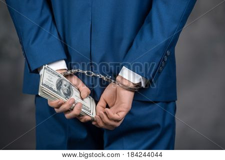 Male person catching in handcuffs holding money finance corruption