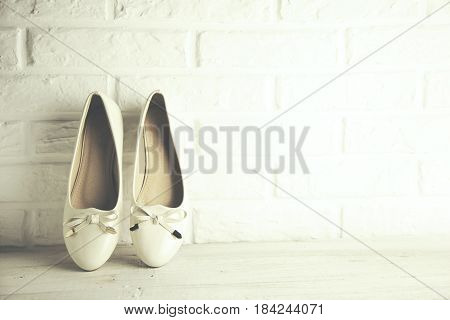 woman white shoes on brick wall background