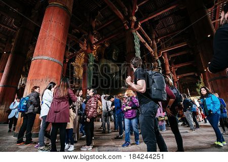 NARA JAPAN - April 10 2017: Tourist sight seeing The great buddha (Daibutsu) in grand hall of at Todaiji temple the biggest wooden temple in the world.