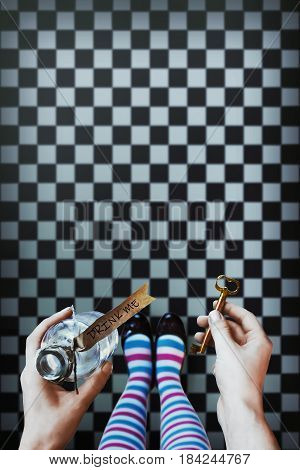 Alice in wonderland. Background. A key and a potion in hands against a  chess floor