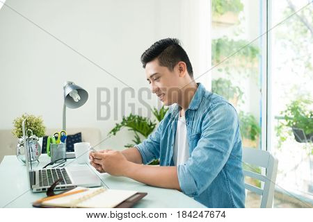 Portrait Of Handsome Asian Young Business Man Holding Mobile Phone And Working On Laptop Computer At