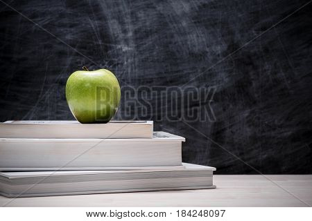 Apple On Top Of Books With Chalkboard.