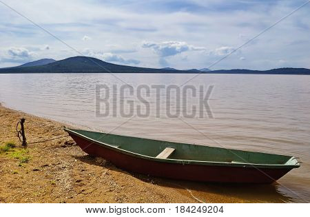 Summer water mountain landscape - mountains Lukash and Nurgush on the shore of Zyuratkul Lake, Southern Urals, Russia. Summer landscape view of mountains and lake waters.Summer water mountain background. Mountains on the horizon and boat near the water