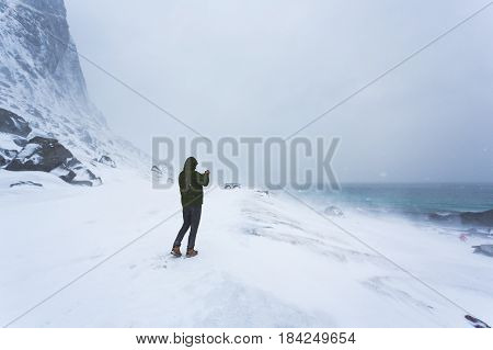 The man takes a picture using the phone of the winter landscape of Lofoten during the blizzard