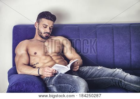 Handsome shirtless muscular bodybuilder man reading book while laying on couch