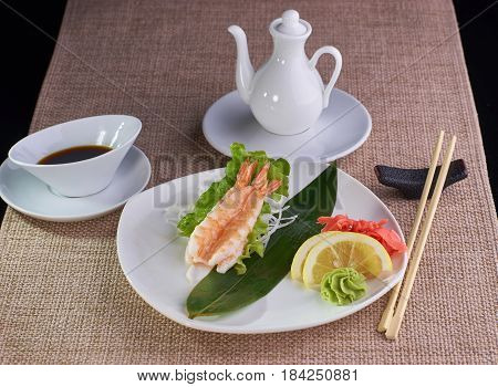 Japanese cuisine. Sashimi with tiger shrimps served with soy sauce and chopsticks on table.