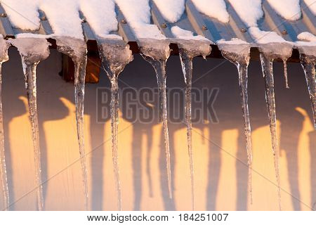 Icicles on the roof of the house at sunset .