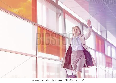 Young businesswoman with luggage running in railroad station