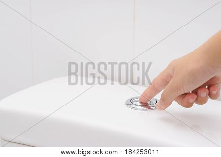 Close up of finger pushing a flush toilet button for cleaning. - save water concept