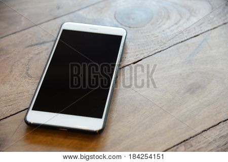 White Smart phone in black case on the wood table prepared for management teams to contact with customer in business