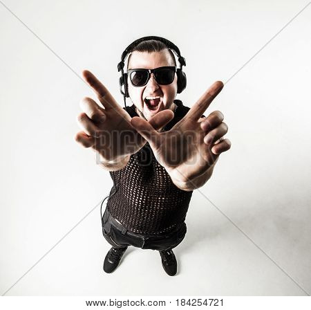 view from the top - DJ - rapper in a stylish t-shirt with headphones and with hands up on white background . the photo has a empty space for your text