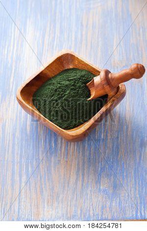Ground  Spirulina powder on wood background