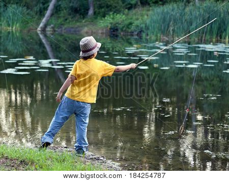 Happy boy go fishing on the river, one boy fisherman with a fishing rod on the shore of the lake, child vacations