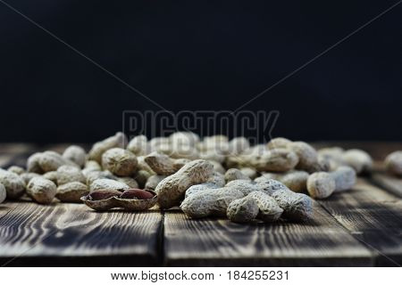 Peanut in sacks. Black background with wood.