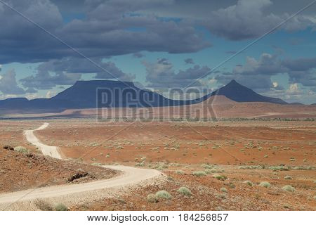 Gravel road at Damaraland with Grootberg mountains in the distance Namibia Africa
