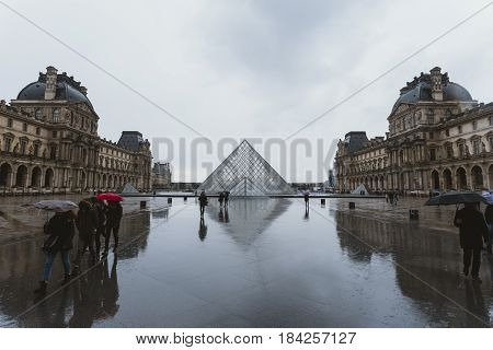 Paris, France - March 2017. People Entering The Pyramid Of The Louvre Art Museum. Tourists Walking W