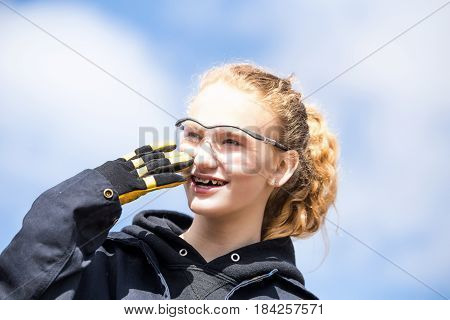 Close up of a teenage girl with long hair in a pnoytail wearing safety glasses and work gloves laughing with hor mouth open and braces on her teeth