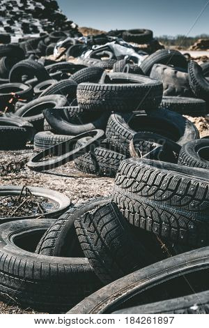 Pile of old rotten rubber tires background, vertical image