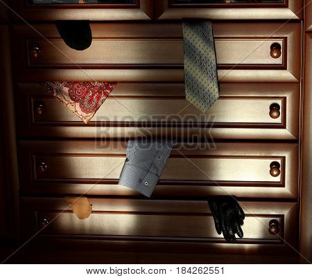 The image of brown wooden dresser. Pieces of clothing in opened drawers