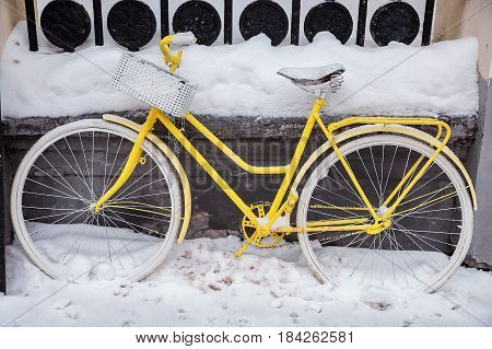 Motionless yellow bicycle with white wheels and basket in the snow
