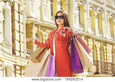 Shopping Beauty. Portrait Of Attractive And Beautiful Woman In Red Coat Posing With Shopping Bags. U