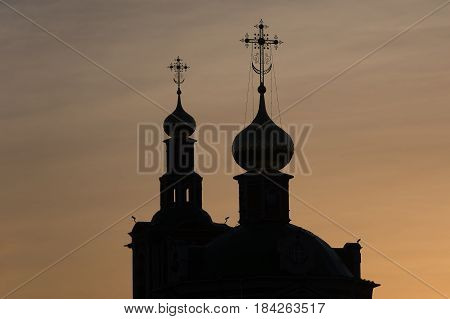Photo of an Orthodox Christian cross on a background of gloomy clouds