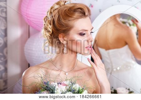 Beautiful bride with fashion wedding hairstyle and bouquet. Closeup portrait of young gorgeous bride. Wedding beauty. Studio shot
