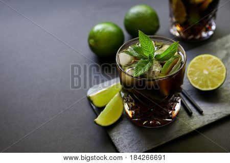 Cuba Libre or long island iced tea cocktail with strong drinks, cola, lime and ice in glasss, cold longdrink on dark background, copy space. Horizontal.