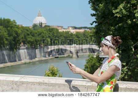 Tourist woman in flower sundress with tablet in hands is standing at Rome bridges and masterpiece dome background