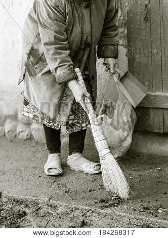 Woman sweeping the yard with a broom .