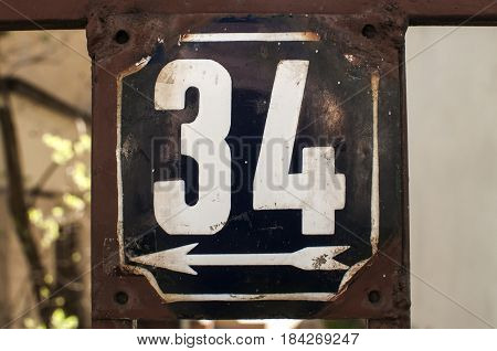 Weathered grunge square metal enameled plate of number of street address with number 34 closeup