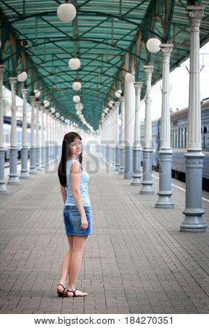 A young girl at a train station near the blue train. Waiting for the passenger. A searching look. Blue train standing at the platform. Clothing girls blue. Columns on the platform of gray-blue color. Blur the background