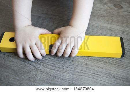 spirit level in young boy hand - child with waterlevel wood floor