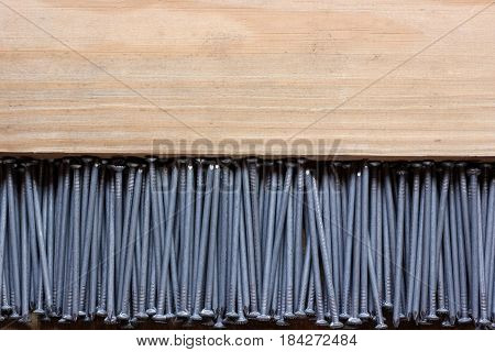 background of roofing nails on a wooden platform top view. empty place for Your text at the top.