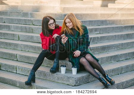 Girls walking around town on a sunny day with phones sitting on a bench and drink coffee