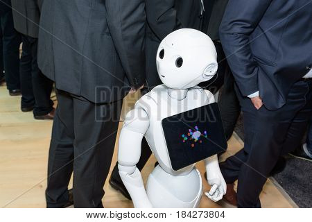 Hannover Germany - March 22 2017: The humanoid robot Pepper from SoftBank Group between men in suits at the ibm booth on CeBIT 2017. CeBIT is the world's largest trade fair for information technology.
