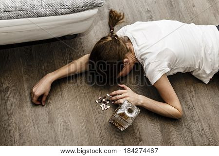 Drunk Or Poisoned Young Woman With Bottle Of Alcohol And Pills