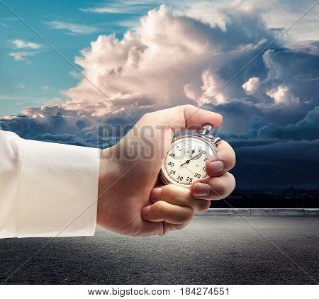 Stopwatch In Male Hand On Dark Sky