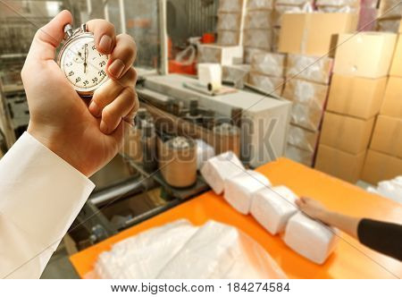 Process Of Paper Products Manufacturing And Stopwatch In Hand