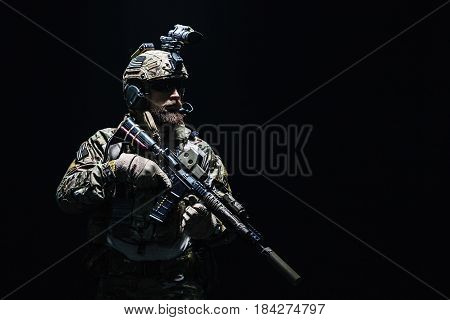 Bearded soldier in Combat Uniforms with weapon, plate carrier and combat helmet are on. Studio shot, dark background