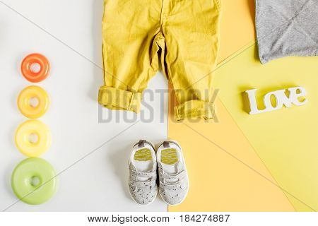 kid stylish set with toys and clothes white and yellow colored background top view