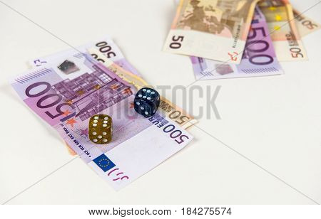 Five hundred and fifty Euro banknotes and dices on a white table. Concept of gambling.
