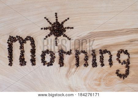 Word morning laid out from coffee grains on wooden background