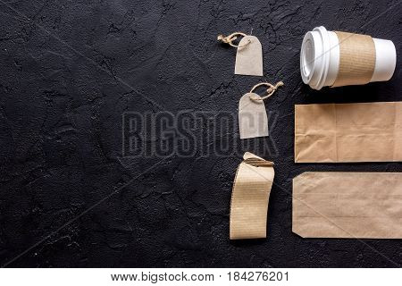 paper bags and plastic cup for take away set on restourant black table background top view space for text
