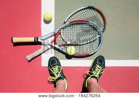 Tennis concept with two rackets, balls and player legs. Sport background