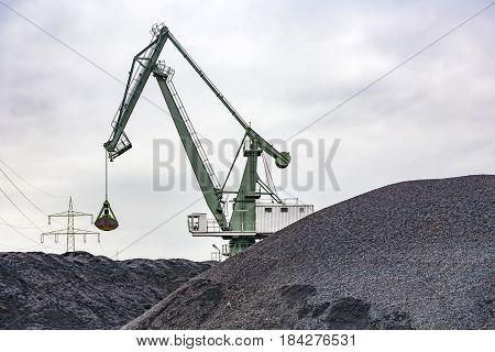 bagger at a huge black charcoal hill