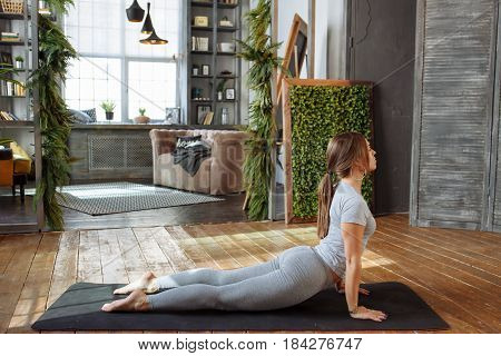 Young woman in homeware practicing balance yoga pose on carpet in her comfy bedroom