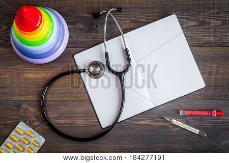 Pediatrics equipment with toys, copybook, stethoscope on wooden table background top view space for text