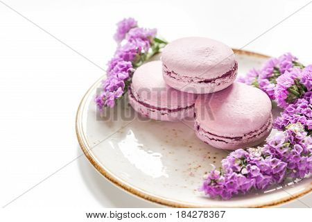 lady morning with macaroons and mauve flowers on white desk background