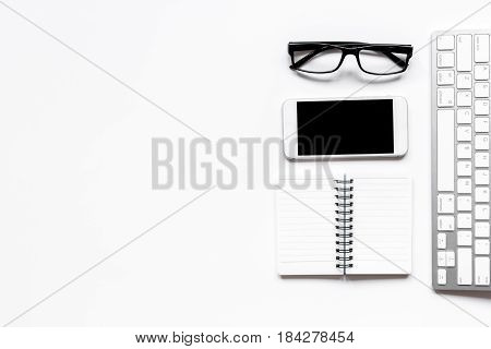 office desk design with keyboard, phone, glasses on white background top view space for text
